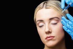 Injektion för kvinnahäleribotox på hennes panna Arkivfoton
