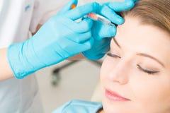 Injektionsspruta för behandling för brunnsort för Botox kvinnautfyllnadsgods ansikts- ung royaltyfria bilder