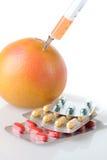 Injektionsspruta i frukt och droger royaltyfria bilder