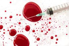 Injektionsspruta med blodfärgstänk Royaltyfri Bild