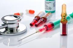Injektionsspruta med små medicinflaskor och läkarbehandlingar Royaltyfria Bilder