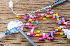 Injektionsspruta och preventivpillerar som symboler Arkivbild