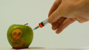 Injektionsspruta som sätts in in i ett grönt äpple med en inristad skalle, representativ bild av bruket av gmo-vikter i mat arkivfilmer