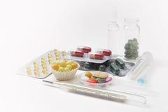 Injektionsspruta, termometer, minnestavlor och kapslar i isolerade blåsor Fotografering för Bildbyråer