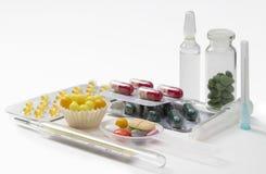 Injektionsspruta, termometer, minnestavlor och kapslar i isolerade blåsor Arkivbilder