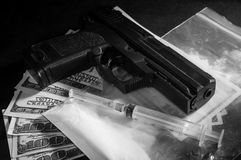 Injektionssprutan och vapnet på drogen hänger löst med pengar Arkivfoto