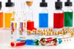 Injektionssprutor med läkarbehandlingen, ampuller och små medicinflaskor, blåsapacke och flaskor med kulör vätska på vit bakgrund Royaltyfria Bilder