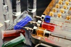 Injektionssprutor med läkarbehandlingen på sterilisering boxas, ampuller och små medicinflaskor med vätska på glansig yttersida t Royaltyfria Foton
