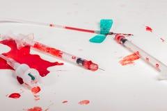 Injektionssprutor och droppen fodrar dolt med blod royaltyfri foto