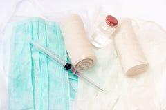 Injektionssprutor och förbinder på kirurgisk maskering och handskar Arkivfoton