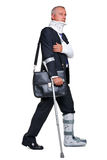Injred businessman on crutches on white. Photo of a badly injured businessman walking on cructhes carrying a briefcase, on a white background stock image