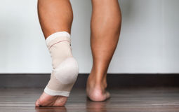 Injured ankle and foot wrapped in bandage Stock Image
