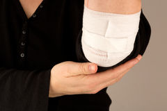 Injured arm. Holding arm with bandage in the hand Royalty Free Stock Photos