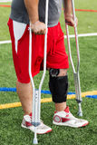 Injured athlete in a knee brace on crutches. An injured player is on the sidelines wearing a knee brace and using crutches after he has had knee surgery Royalty Free Stock Photo