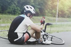 Injured biker holding his smartphone calling rescue team Royalty Free Stock Images