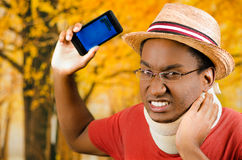 Injured black hispanic male wearing neck brace, glasses and hat, holding cell phone making painful facial expression Royalty Free Stock Image