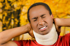 Injured black hispanic male wearing neck brace, holding hands in pain around support making faces of agony, yellow. Abstract background Royalty Free Stock Photos