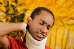 Injured black hispanic male wearing neck brace, holding hands in pain around support making faces of agony, yellow Stock Photo