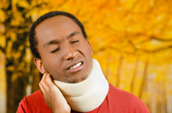 Injured black hispanic male wearing neck brace, holding hands in pain around support making faces of agony, yellow. Abstract background Stock Images