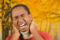 Injured black hispanic male wearing neck brace, holding hands in pain around support making faces of agony, yellow. Abstract background Stock Photo