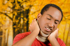Injured black hispanic male wearing neck brace, holding hands in pain around support making faces of agony, yellow. Abstract background Stock Photography