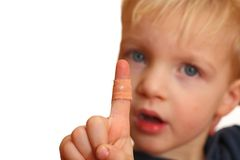 Injured boy. Portrait of a young boy showing a plaster on his injured finger Stock Photo