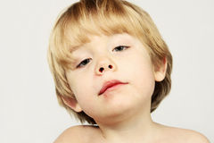 An injured boy with an attitude. Young boy with a fat lip after falling down Royalty Free Stock Photos