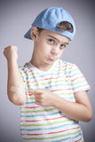 Injured boy with a a bruised elbow reacts in pain. Boy in pain with wounded arm and band aid in hand Royalty Free Stock Photos