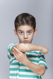 Injured boy with a a bruised elbow reacts in pain. Boy in pain with wounded arm and band aid in hand Royalty Free Stock Photo
