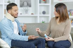 Injured boyfriend and girlfriend giving him pill Stock Images