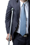 Injured businessman with crutches, insurance concept Stock Photography