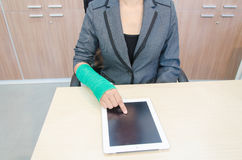 Injured businesswoman with broken hand  and green cast on the wr Stock Images