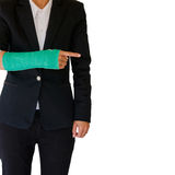 Injured businesswoman with green cast on hand and arm isolated o Stock Photography