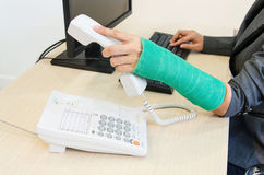 Injured businesswoman with green cast on the wrist holding telep Royalty Free Stock Photos