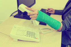 Injured businesswoman with green cast on the wrist holding telep Royalty Free Stock Image