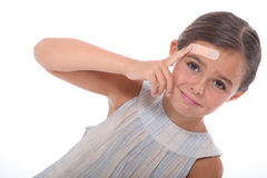 Injured child. With a plaster on her forehead Royalty Free Stock Image