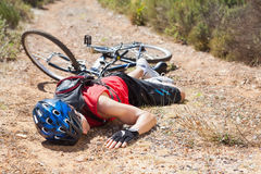 Injured cyclist lying on ground after a crash Royalty Free Stock Image