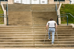 Injured determination. Man on crutches climbs a big set of stairs Royalty Free Stock Image