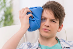 Injured eye. Depressed teenage boy holding a cold bag on the injured eye while sitting on the couch royalty free stock images