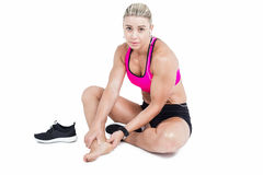 Injured female athlete sitting and touching ankle Stock Photos