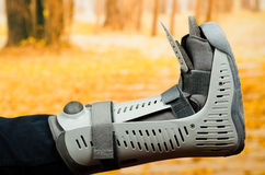 Injured foot wearing extensive grey plastic protection case in front of autumn background Stock Images