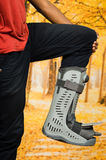 Injured foot wearing extensive grey plastic protection case in front of autumn background Royalty Free Stock Photo