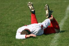 Injured football player. A football player laying injured on the grass Royalty Free Stock Photo