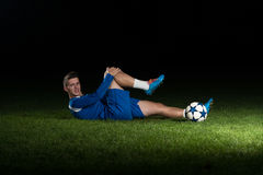 Injured Football Player Lying On The Ground Royalty Free Stock Photos