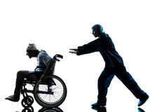 Injured funny man in wheelchair escaping away of nurse silhouett. One injured men in wheelchair escaping away of nurse in silhouette studio on white background Stock Photos