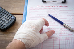 Injured hand filling a insurance claim form Stock Images