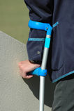 Injured and handicapped. A white hand of a caucasian handicapped man holding a crutch and standing outdoors waiting for recovery after having an accident Royalty Free Stock Photos