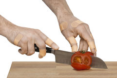Injured hands with knife cutting a tomato Royalty Free Stock Image