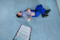 Injured Handyman Lying On Floor stock photo