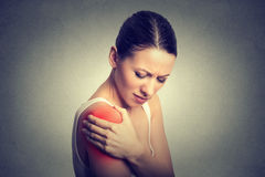 Injured joint. Woman patient in pain having painful shoulder colored in red Royalty Free Stock Photo